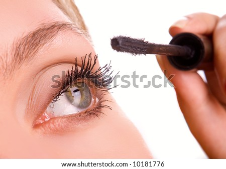 young woman applying cosmetics on eyelashes close-up