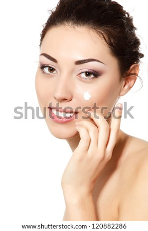 young woman applying cream on face, over white background