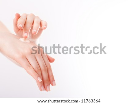 Young woman applying cream on her hands. - stock photo