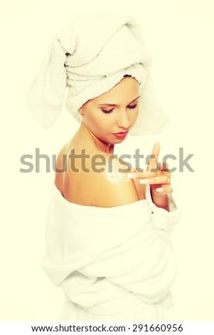 Young woman applying cream on shoulders - stock photo