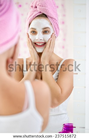 Young  woman applying facial cleansing mask, beauty treatments - stock photo