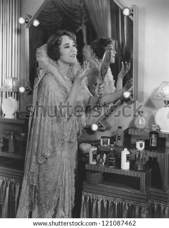 Young woman applying lip balm by dressing table