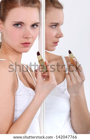 Young woman applying lipstick in a mirror - stock photo