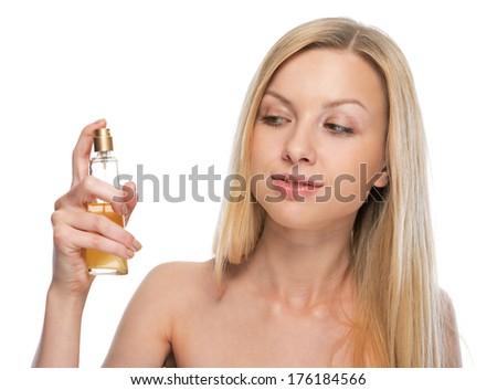 Young woman applying perfume - stock photo