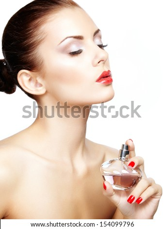 Young woman applying perfume on herself isolated on white background. Fashion photo - stock photo