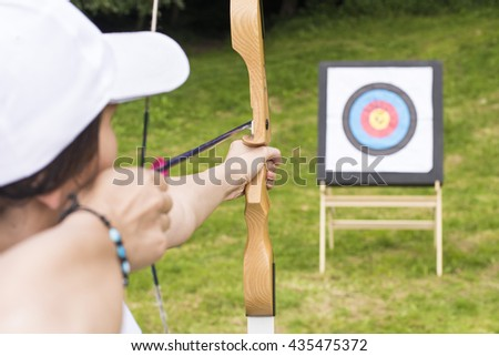 Young woman archer holds his bow aiming at a target. Sport, recreation and healthy lifestyle concept. - stock photo
