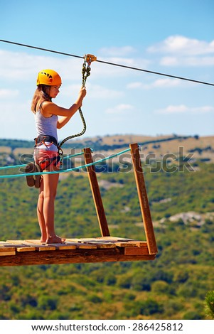young woman are ready to descend on zipline in mountain, extreme sport - stock photo