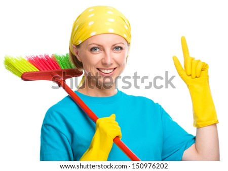 Young woman as a cleaning maid holding broom and pointing up, isolated over white - stock photo