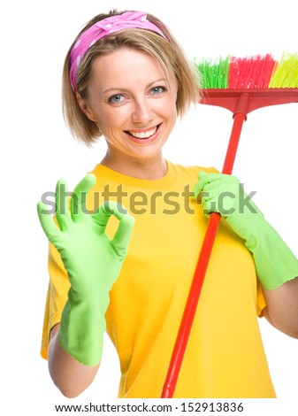 Young woman as a cleaning maid holding broom and showing OK sign, isolated over white - stock photo