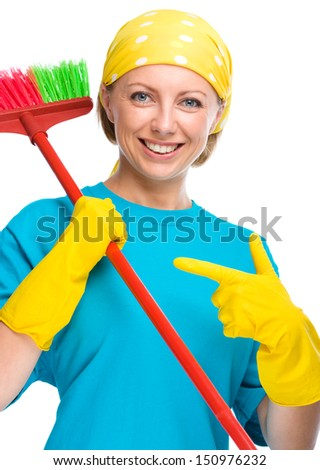 Young woman as a cleaning maid holding broom while pointing to the right, isolated over white - stock photo