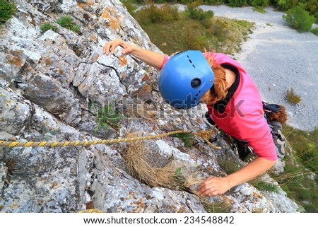 Young woman ascending a steep wall on limestone cliff - stock photo