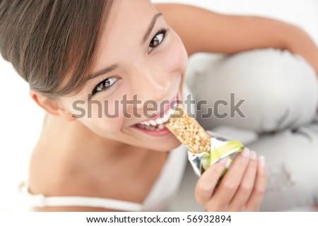 Young woman asian caucasian eating healthy muesli bar. - stock photo