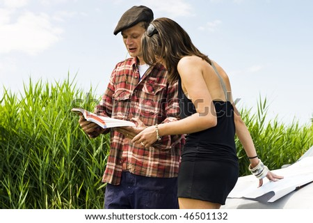 Young woman asking a farmer for information using a guide book and leaning on a map on the hood of her car - stock photo