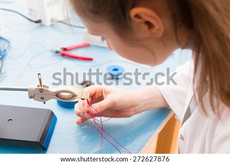 Young woman assemble optic sensor for intelligent robot system - stock photo