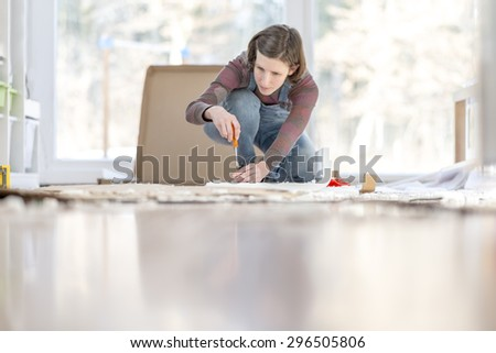 Young Woman assembling a DIY furniture at home kneeling on the floor in front of a bright glass window surrounded by materials and tools working with a screwdriver. Focus on the screwdriver. - stock photo