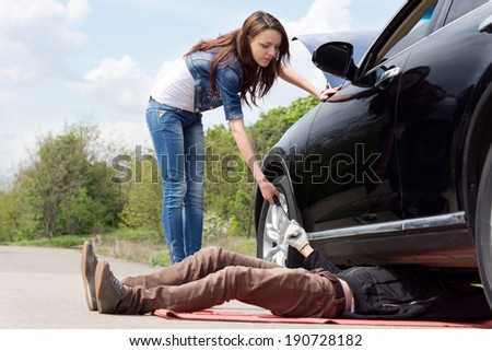 Young woman assisting a mechanic working on the underside of her car after she breaks down at the side of a rural road - stock photo