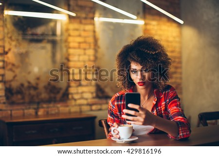 Young woman at cafe drinking coffee and using mobile phone  - stock photo
