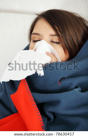 Young woman at home having flu, wrapped up in blanket, sneezing. - stock photo