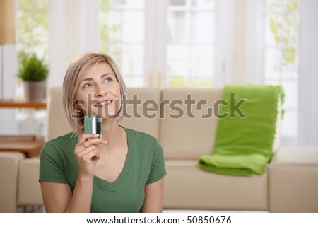 Young woman at home holding credit card looking up thinking about shopping. - stock photo
