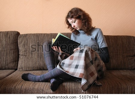 Young woman at home reading a book, sitting on brown sofa - stock photo