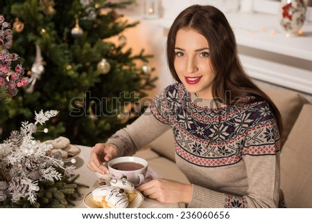 Young woman at home sipping tea from a cup and eating cookies while sitting on couch near Christmas tree - stock photo