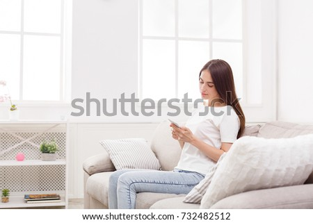 Young woman at home with smartphone in light livingroom. Copy space