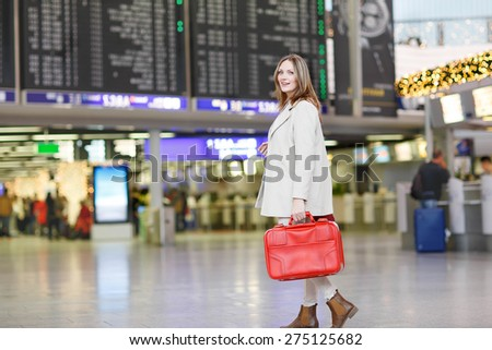 Young woman  at international airport, checking electronic board and waiting for her flight. Female passenger with red suitcase walking through departure terminal, indoors. - stock photo