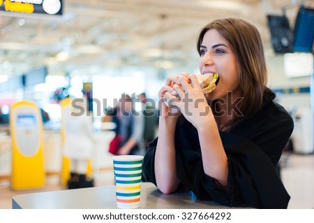 Young woman at international airport, drinking coffee and eating a sandwich while waiting for her flight. Female passenger at terminal, indoors. - stock photo