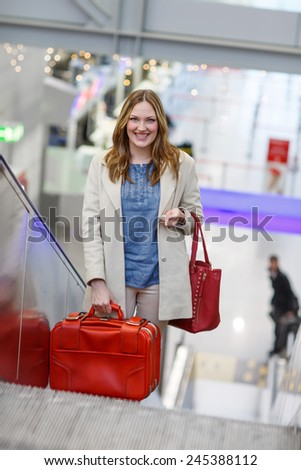 Young woman at international airport, on escalator at arrival terminal . Female passenger looking forward to arrive home, indoors. - stock photo