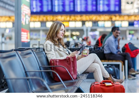 Young woman at international airport, reading her ebook computer and drinking coffee to go while waiting for her flight. Female passenger at terminal, indoors. - stock photo