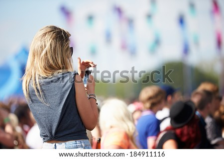 Young Woman At Outdoor Music Festival Using Mobile Phone - stock photo
