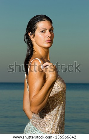Young woman at the beach wearing a golden top shirt in the summertime