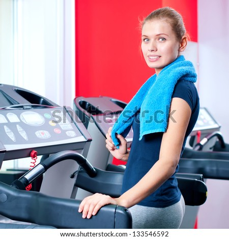 Young woman at the gym exercising. Run on machine