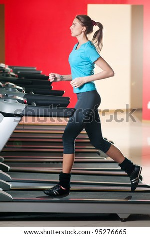 Young woman at the gym exercising. Run on on a machine. - stock photo