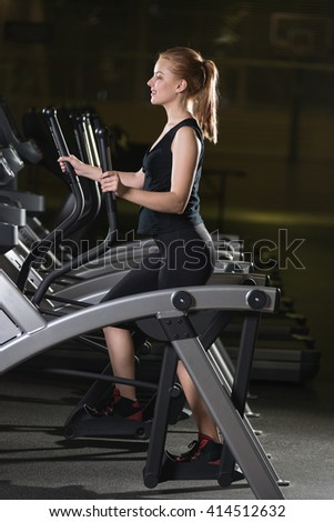 Young woman at the gym exercising. Run on on a machine. Jogging workout in dark fitness club. Cardio. - stock photo