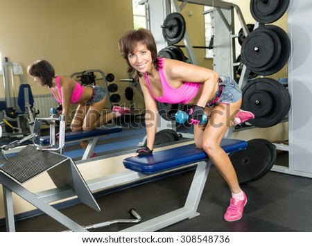 Young woman at the gym with dumbbells