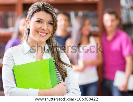 Young woman at the library holding a notebook - stock photo