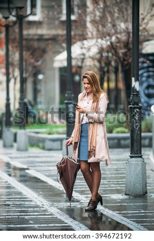 Young woman at the street using her mobile phone  - stock photo