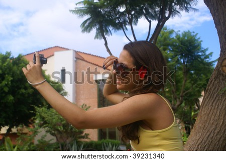 Young woman at the vacation taking pictures of herself with a digital camera .