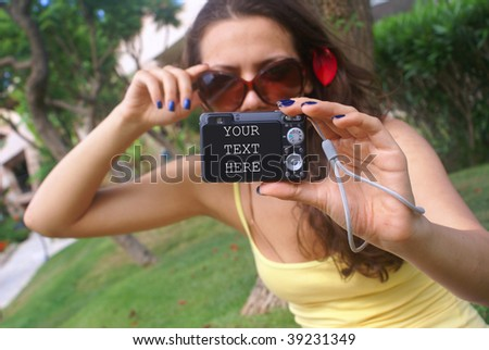 Young woman at the vacation taking pictures of herself with a digital camera . - stock photo
