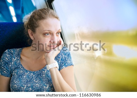 young woman at the window of a train - stock photo