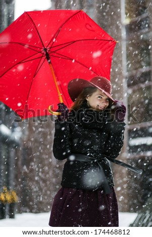 Young woman at winter day with red umbrella - stock photo