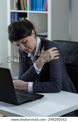 Young woman at work and throbbing pain in arm - stock photo