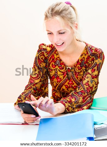 Young woman at work distracted by the phone - stock photo