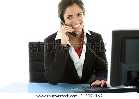 Young woman at workplace. She is a brown hair and brown eyes pretty girl using phone at the office and she looks at the camera. She wears a black formal jacket over a white shirt.