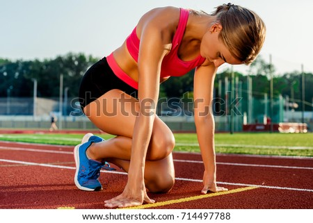 Young Woman Athlete At Starting Position Ready To Start A Race On Racetrack