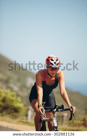 Young woman athlete cycling on country road. Woman riding bicycle practicing for triathlon competition. - stock photo