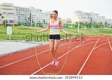 Young woman athlete jumping on a skipping rope before running on a stadium running track with university campus on background. Warming up before workout