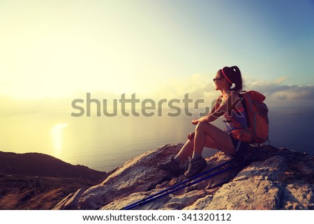 young woman backpacker at sunrise seaside mountain peak
