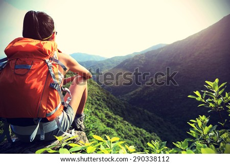 young woman backpacker  enjoy the view at mountain peak,vintage effect  - stock photo